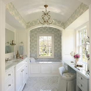 Exemple d'une grand salle de bain principale chic avec un plan de toilette en marbre, un sol en marbre, un placard à porte shaker, des portes de placard blanches, une baignoire en alcôve, un mur blanc, un lavabo encastré et un plan de toilette gris.