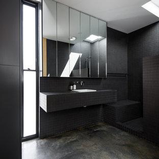 パースの小さいモダンスタイルのおしゃれなマスターバスルーム (一体型シンク、黒いキャビネット、タイルの洗面台、オープン型シャワー、一体型トイレ、黒いタイル、セラミックタイル、黒い壁、コンクリートの床) の写真