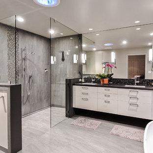 Idee per una stanza da bagno padronale american style di medie dimensioni con ante lisce, ante bianche, vasca freestanding, doccia ad angolo, piastrelle grigie, piastrelle in ceramica, pareti grigie, pavimento con piastrelle in ceramica e top in granito