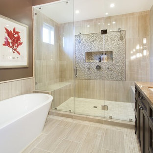 This is an example of a mid-sized mediterranean master bathroom in San Francisco with a freestanding tub, beige floor, recessed-panel cabinets, dark wood cabinets, an alcove shower, multi-coloured tile, mosaic tile, brown walls, porcelain floors, an undermount sink, granite benchtops, brown benchtops, a niche and a shower seat.