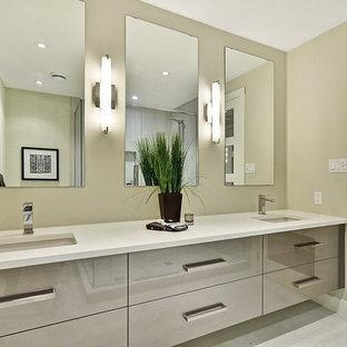 Стильный дизайн: большая главная ванная комната в современном стиле с плоскими фасадами, бежевыми фасадами, душем в нише, серой плиткой, керамогранитной плиткой, бежевыми стенами, полом из ламината, врезной раковиной, столешницей из искусственного камня, серым полом, душем с распашными дверями и белой столешницей - последний тренд