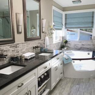 Foto på ett amerikanskt en-suite badrum, med skåp i shakerstil, vita skåp, ett hörnbadkar, en hörndusch, en toalettstol med hel cisternkåpa, grå kakel, mosaik, grå väggar, klinkergolv i keramik, ett undermonterad handfat, bänkskiva i kvarts, grått golv och dusch med gångjärnsdörr