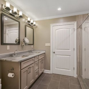 Example of a mid-sized transitional master gray tile and porcelain tile porcelain floor and gray floor bathroom design in New Orleans with shaker cabinets, gray cabinets, a two-piece toilet, gray walls, an undermount sink, quartzite countertops and a hinged shower door