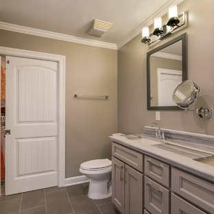 Bathroom - mid-sized transitional master gray tile and porcelain tile porcelain floor and gray floor bathroom idea in New Orleans with shaker cabinets, gray cabinets, a two-piece toilet, gray walls, an undermount sink, quartzite countertops and a hinged shower door