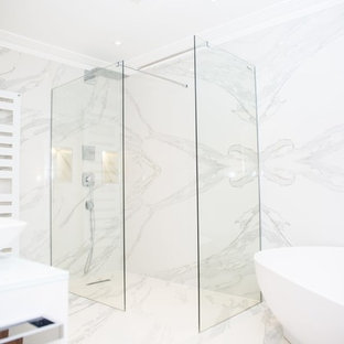 Design ideas for a large modern family bathroom in London with flat-panel cabinets, white cabinets, a freestanding bath, a walk-in shower, a wall mounted toilet, brown tiles, stone slabs, multi-coloured walls, marble flooring, a submerged sink, glass worktops, multi-coloured floors and an open shower.