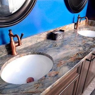 Foto de cuarto de baño principal, actual, grande, con puertas de armario de madera en tonos medios, bañera exenta, ducha abierta, sanitario de dos piezas, baldosas y/o azulejos grises, baldosas y/o azulejos de porcelana, paredes azules, suelo de baldosas de porcelana, lavabo bajoencimera, encimera de granito, suelo gris, ducha abierta y encimeras beige