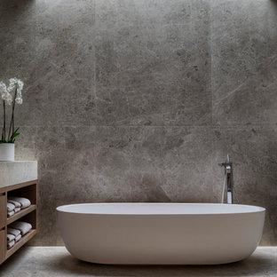 Aménagement d'une très grand salle de bain principale contemporaine avec un placard à porte plane, des portes de placard en bois brun, une baignoire indépendante, un espace douche bain, un WC suspendu, un carrelage gris, du carrelage en marbre, un mur gris, un sol en marbre, un lavabo posé, un plan de toilette en marbre, un sol gris, une cabine de douche à porte coulissante, un plan de toilette gris, meuble double vasque, meuble-lavabo encastré et un plafond à caissons.