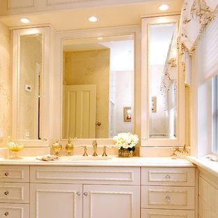ニューヨークの大きいトラディショナルスタイルのおしゃれなマスターバスルーム (白いキャビネット、レイズドパネル扉のキャビネット、ベージュのタイル、白い壁、セラミックタイルの床、アンダーカウンター洗面器) の写真