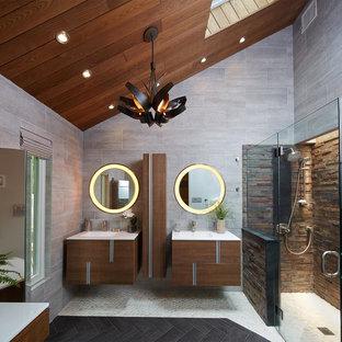 Foto de cuarto de baño principal, actual, pequeño, con armarios tipo mueble, puertas de armario de madera oscura, encimera de acrílico, ducha a ras de suelo, sanitario de pared, baldosas y/o azulejos negros y suelo de baldosas tipo guijarro