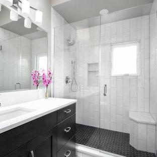Ispirazione per una stanza da bagno padronale minimalista di medie dimensioni con ante in stile shaker, ante nere, doccia alcova, WC a due pezzi, piastrelle bianche, piastrelle in gres porcellanato, pareti grigie, pavimento in gres porcellanato, lavabo sottopiano, top in quarzo composito, pavimento grigio, porta doccia a battente, top bianco, panca da doccia, un lavabo e mobile bagno incassato
