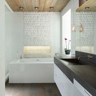 Foto di una stanza da bagno minimal con ante lisce, ante bianche, piastrelle bianche, parquet scuro, lavabo integrato, vasca sottopiano e top grigio