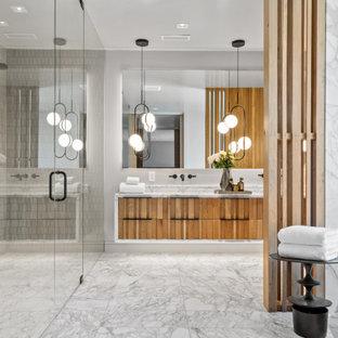 Источник вдохновения для домашнего уюта: большая главная ванная комната в современном стиле с фасадами с филенкой типа жалюзи, фасадами цвета дерева среднего тона, отдельно стоящей ванной, душем без бортиков, инсталляцией, бежевой плиткой, керамической плиткой, желтыми стенами, мраморным полом, накладной раковиной, мраморной столешницей, желтым полом, душем с распашными дверями, желтой столешницей, унитазом, тумбой под две раковины и подвесной тумбой