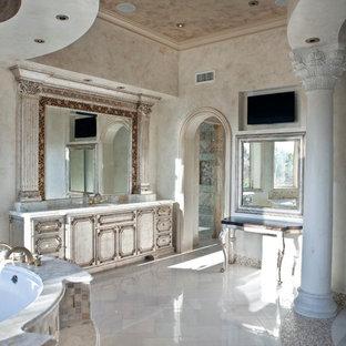 Свежая идея для дизайна: большая главная ванная комната в средиземноморском стиле с фасадами с выступающей филенкой, искусственно-состаренными фасадами, угловой ванной, душевой комнатой, раздельным унитазом, разноцветной плиткой, цементной плиткой, бежевыми стенами, полом из известняка, врезной раковиной, столешницей из кварцита, белым полом и душем с распашными дверями - отличное фото интерьера