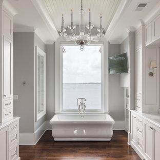 Ejemplo de cuarto de baño principal, tradicional, con armarios con paneles empotrados, puertas de armario beige, bañera exenta, paredes grises, suelo de madera en tonos medios y lavabo bajoencimera