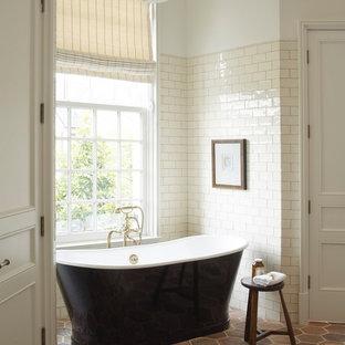 Large elegant master beige tile and porcelain tile multicolored floor and terra-cotta floor freestanding bathtub photo in Houston with beige walls