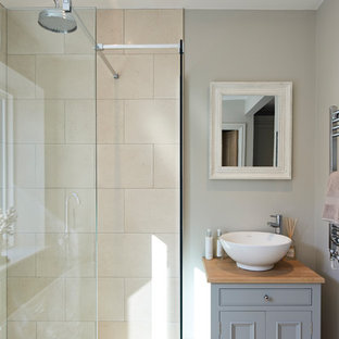 Photo of a traditional shower room bathroom in Hertfordshire with recessed-panel cabinets, grey cabinets, a corner shower, beige tiles, grey walls, a vessel sink, wooden worktops and brown worktops.