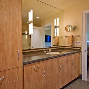 Ispirazione per una stanza da bagno minimalista di medie dimensioni con lavabo sottopiano, ante lisce, ante in legno chiaro, top in pietra calcarea, vasca ad alcova, vasca/doccia, WC monopezzo, piastrelle grigie, piastrelle in pietra, pareti beige e pavimento in gres porcellanato