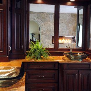 Modelo de cuarto de baño principal, clásico, grande, con armarios con paneles con relieve, puertas de armario de madera en tonos medios, ducha empotrada, sanitario de dos piezas, baldosas y/o azulejos beige, baldosas y/o azulejos de piedra, paredes grises, suelo de travertino, lavabo sobreencimera y encimera de ónix