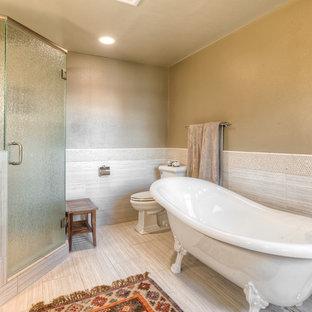 シアトルの大きいおしゃれなマスターバスルーム (落し込みパネル扉のキャビネット、濃色木目調キャビネット、猫足浴槽、コーナー設置型シャワー、一体型トイレ、ベージュのタイル、石タイル、緑の壁、アンダーカウンター洗面器、珪岩の洗面台) の写真