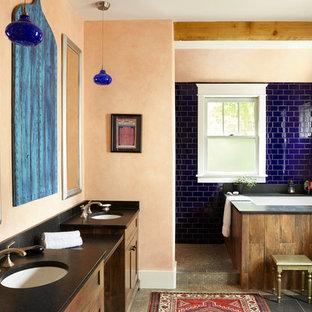 ナッシュビルの中サイズの地中海スタイルのおしゃれなマスターバスルーム (落し込みパネル扉のキャビネット、濃色木目調キャビネット、和式浴槽、青いタイル、サブウェイタイル、アンダーカウンター洗面器、珪岩の洗面台、グレーの床、オレンジの壁) の写真