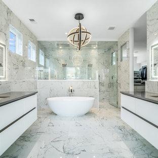 На фото: большая главная ванная комната в современном стиле с плоскими фасадами, белыми фасадами, японской ванной, двойным душем, унитазом-моноблоком, серой плиткой, душем с распашными дверями, сиденьем для душа, тумбой под две раковины, подвесной тумбой, мраморной плиткой, серыми стенами, мраморным полом, врезной раковиной, мраморной столешницей, серым полом и серой столешницей с