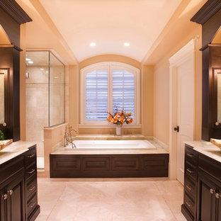 Новый формат декора квартиры: большая главная ванная комната в классическом стиле с настольной раковиной, темными деревянными фасадами, мраморной столешницей, угловым душем, бежевыми стенами, накладной ванной, плиткой из травертина, полом из керамогранита, бежевым полом и душем с распашными дверями
