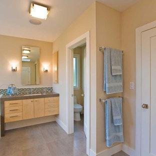 Стильный дизайн: огромная ванная комната в современном стиле с врезной раковиной, плоскими фасадами, светлыми деревянными фасадами, столешницей из искусственного камня, накладной ванной, угловым душем, унитазом-моноблоком, серой плиткой, керамогранитной плиткой, бежевыми стенами, полом из керамогранита и унитазом - последний тренд