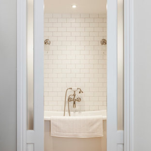 Inspiration for a medium sized beach style ensuite bathroom in London with a freestanding bath, white tiles, ceramic tiles, white walls, light hardwood flooring and a wall-mounted sink.