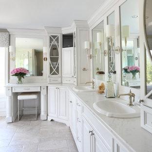 Idée de décoration pour une très grande salle de bain principale tradition avec un placard avec porte à panneau surélevé, des portes de placard blanches, un sol en carrelage de porcelaine, un lavabo encastré, un sol beige et un plan de toilette blanc.