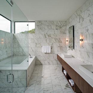 Foto di una stanza da bagno padronale contemporanea di medie dimensioni con lavabo a bacinella, ante lisce, ante in legno bruno, vasca da incasso, doccia a filo pavimento, pistrelle in bianco e nero e piastrelle in pietra