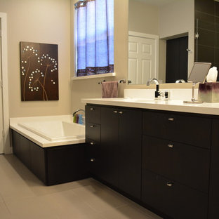 Immagine di una stanza da bagno padronale minimal di medie dimensioni con ante lisce, ante nere, vasca ad alcova, doccia ad angolo, WC monopezzo, piastrelle nere, piastrelle di cemento, pareti beige, pavimento con piastrelle in ceramica, lavabo sottopiano e top in superficie solida