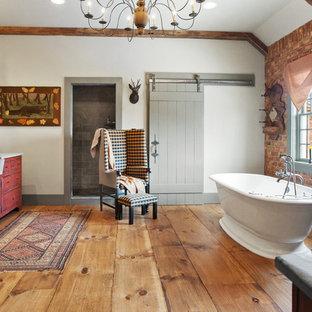 Inredning av ett rustikt en-suite badrum, med vita väggar, röda skåp, ett fristående badkar och mellanmörkt trägolv