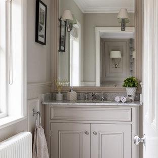 На фото: главная ванная комната среднего размера в викторианском стиле с фасадами с декоративным кантом, серыми фасадами, серыми стенами, мраморным полом, монолитной раковиной, мраморной столешницей, белым полом, белой столешницей, тумбой под одну раковину, встроенной тумбой и панелями на части стены