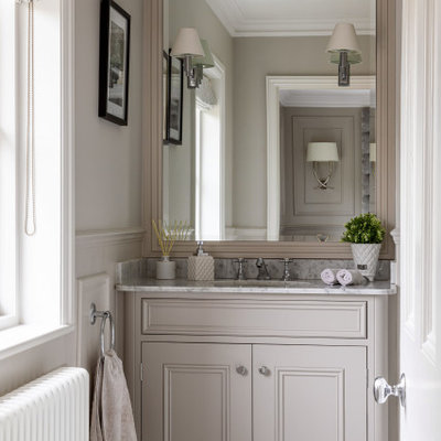 Inspiration for a mid-sized victorian master marble floor, white floor, single-sink and wall paneling bathroom remodel in Essex with beaded inset cabinets, gray cabinets, gray walls, an integrated sink, marble countertops, white countertops and a built-in vanity