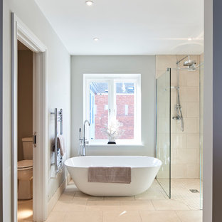 Photo of a classic ensuite bathroom in Hertfordshire with a freestanding bath, a built-in shower, a two-piece toilet, beige tiles, grey walls, beige floors, an open shower and grey worktops.