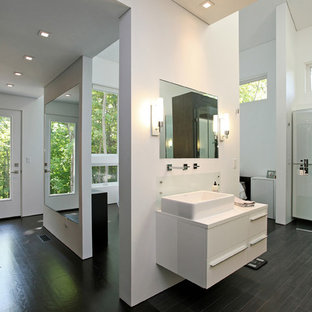 Example of a trendy wood-look tile and black tile dark wood floor doorless shower design in New York with a vessel sink, flat-panel cabinets, laminate countertops, white cabinets, white walls and a one-piece toilet