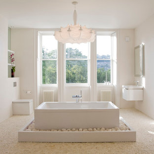 Inspiration for a large modern master white tile and ceramic tile pebble tile floor bathroom remodel in Other with a wall-mount sink, flat-panel cabinets, white cabinets, a one-piece toilet and white walls