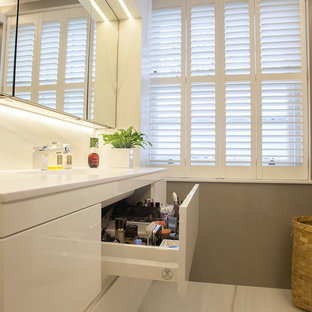 Inspiration for a large contemporary master white tile and marble tile marble floor doorless shower remodel in London with flat-panel cabinets, white cabinets, a one-piece toilet, white walls, a console sink and engineered quartz countertops
