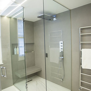 Inspiration for a large contemporary ensuite bathroom in London with flat-panel cabinets, white cabinets, a walk-in shower, a one-piece toilet, white tiles, marble tiles, white walls, marble flooring, a console sink and engineered stone worktops.