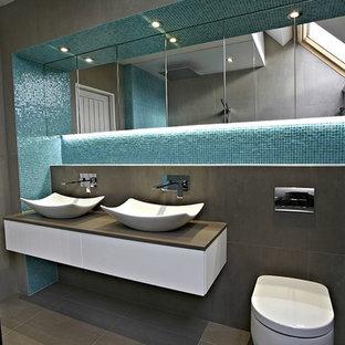 Diseño de cuarto de baño principal, contemporáneo, pequeño, con ducha abierta, sanitario de pared, baldosas y/o azulejos azules, paredes grises, suelo de cemento, lavabo suspendido, puertas de armario marrones, baldosas y/o azulejos en mosaico, encimera de acrílico, suelo gris, ducha abierta y encimeras grises
