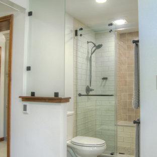 Klassisk inredning av ett mellanstort vit vitt en-suite badrum, med luckor med infälld panel, skåp i mellenmörkt trä, ett fristående badkar, en dusch i en alkov, en toalettstol med hel cisternkåpa, vit kakel, porslinskakel, vita väggar, klinkergolv i porslin, ett undermonterad handfat, bänkskiva i kvartsit, beiget golv och dusch med skjutdörr