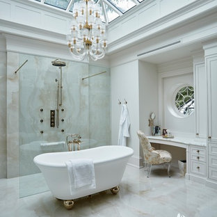 Expansive traditional master bathroom in Toronto with a freestanding tub, beige tile, marble, marble floors, marble benchtops, an open shower, recessed-panel cabinets, white cabinets, a curbless shower, white walls, beige floor and white benchtops.