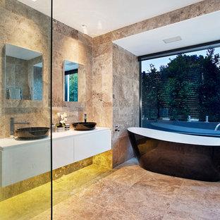Idee per una grande stanza da bagno design con lavabo a bacinella, ante lisce, ante bianche, top in superficie solida, vasca freestanding, doccia aperta, WC sospeso, piastrelle beige, pareti beige, pavimento in travertino, doccia aperta e piastrelle in travertino