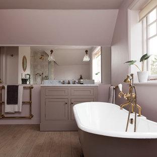 Foto di una stanza da bagno tradizionale con ante in stile shaker, ante viola, vasca con piedi a zampa di leone, pareti viola, pavimento in legno massello medio, pavimento marrone e top bianco
