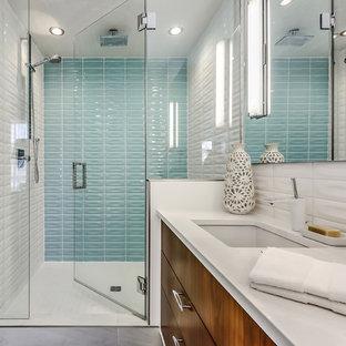 Diseño de cuarto de baño con ducha, vintage, de tamaño medio, con ducha empotrada, baldosas y/o azulejos de cerámica, paredes blancas, suelo de baldosas de porcelana, baldosas y/o azulejos azules, baldosas y/o azulejos blancos, lavabo bajoencimera, encimera de cuarzo compacto, ducha con puerta con bisagras, armarios con paneles lisos, puertas de armario de madera en tonos medios y suelo gris