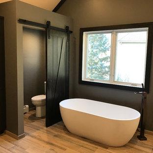 Modelo de cuarto de baño principal, rústico, de tamaño medio, con armarios con paneles lisos, puertas de armario de madera en tonos medios, bañera exenta, sanitario de una pieza, suelo de madera clara, paredes marrones y suelo beige