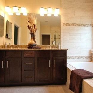 Mittelgroßes Badezimmer En Suite mit Einbauwaschbecken, Schrankfronten mit vertiefter Füllung, dunklen Holzschränken, Granit-Waschbecken/Waschtisch, Eckbadewanne, offener Dusche, beigefarbenen Fliesen, Mosaikfliesen und beiger Wandfarbe in Jacksonville