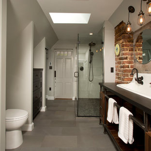 This is an example of a large industrial master bathroom in DC Metro with a trough sink, open cabinets, dark wood cabinets, engineered quartz benchtops, a corner shower, gray tile, porcelain tile, porcelain floors and grey walls.