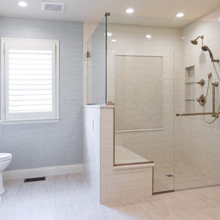 Corner shower - large transitional master beige tile and porcelain tile porcelain floor and beige floor corner shower idea in Kansas City with raised-panel cabinets, white cabinets, a one-piece toilet, blue walls, an undermount sink, engineered quartz countertops, a hinged shower door and beige countertops