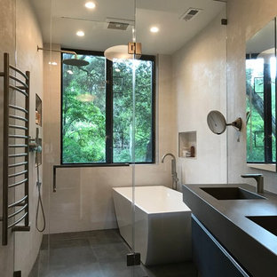 Trendy beige tile porcelain tile and gray floor bathroom photo in San Francisco with flat-panel cabinets, black cabinets, beige walls, an integrated sink, a hinged shower door and gray countertops